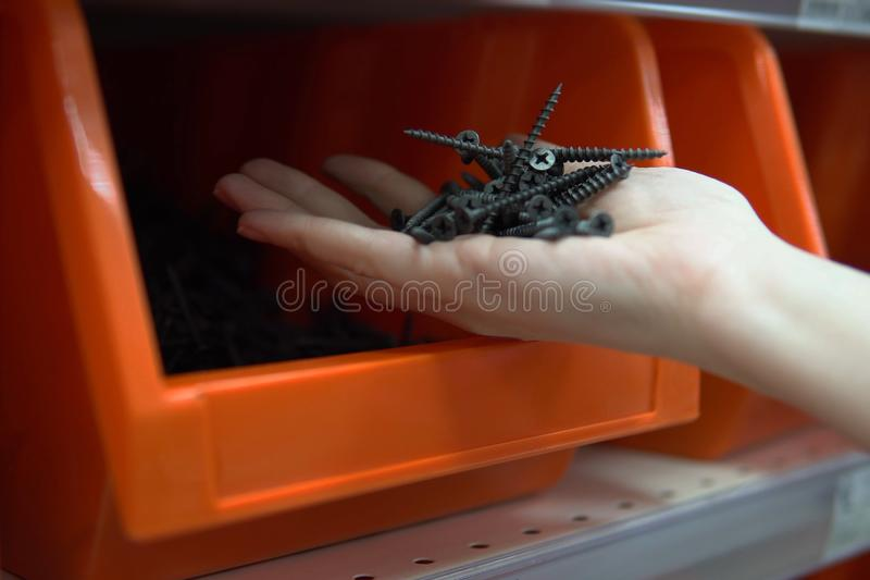 A woman chooses tapping screw in a store of construction goods royalty free stock images