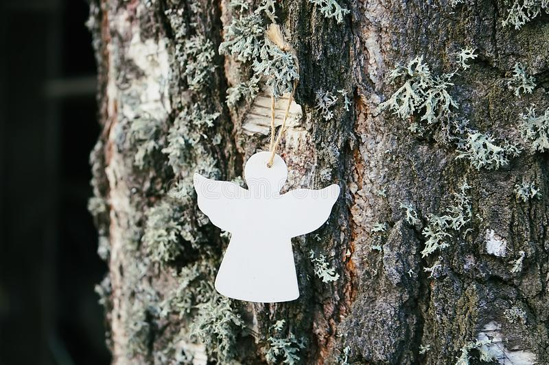 Wooden decoration angel white figure on tree bark stock photo