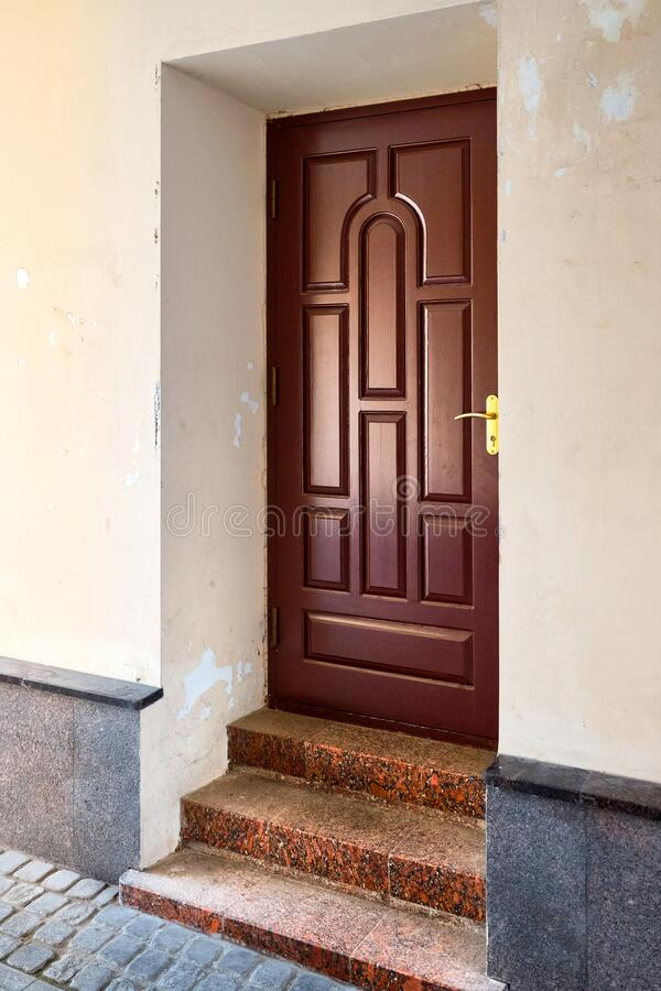 Wooden elegant entrance door with stone red granite threshold and steps at the facade of the building with peeling plaster royalty free stock photo