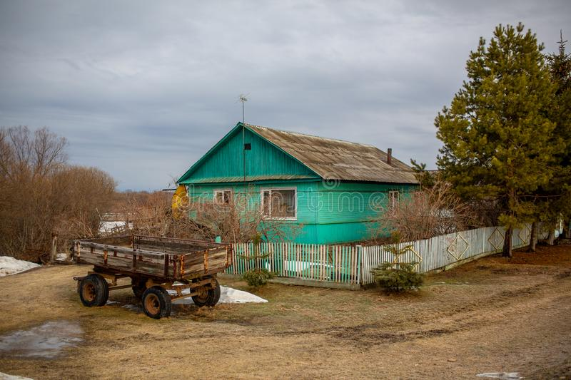 Wooden farmhouse behind a wooden picket fence. Hut in the Russian village. Russian village. Wooden farmhouse behind a wooden picket fence. Hut in the Russian royalty free stock photo