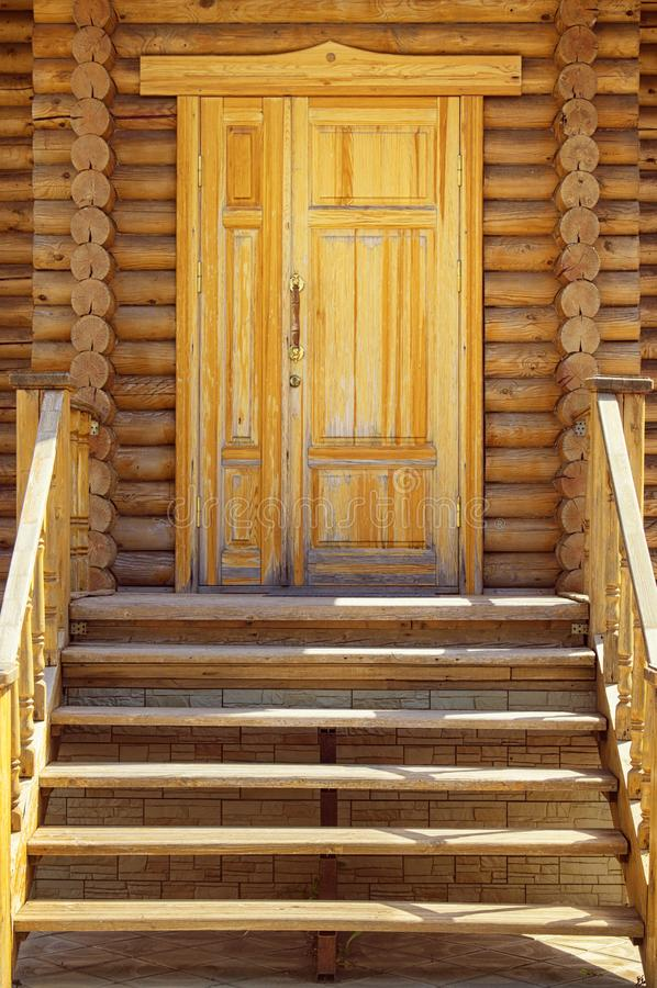 Wooden porch, door and staircase in a log frame house. The ancient technology of building a Russian log hut and churches.  royalty free stock image