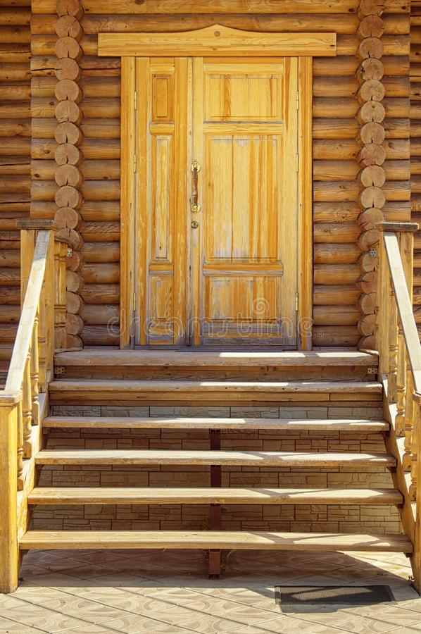 Wooden porch, door and staircase in a log frame house. The ancient technology of building a Russian log hut and churches stock photos