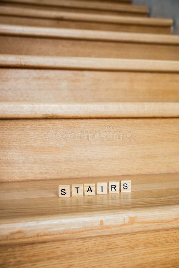 The word Stairs is written in cubic letters on a wooden stairs in house.  royalty free stock photo