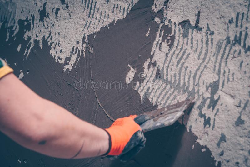 The worker aligns the wall with a tile adhesive applying it with a spatula. Preparation for tiling royalty free stock image