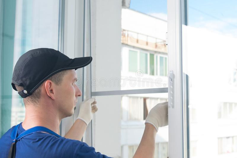 A worker in a blue uniform, rear view, removes a mosquito net from a plastic window frame, against the sky royalty free stock photo