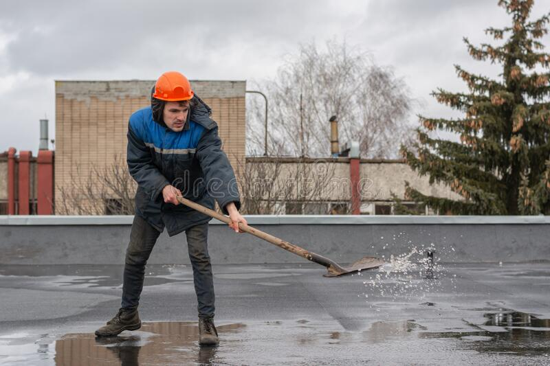 Worker builder on the roof of the factory removes water from the puddle with a shovel. on the head a construction helmet. stock photography