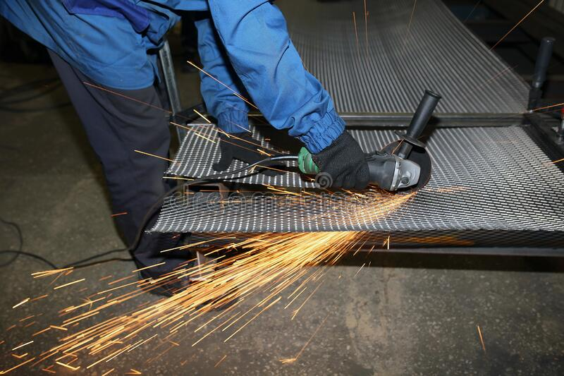 A worker cuts an iron mesh netting with an iron circle. Sparks fly. A worker cuts an iron mesh netting with an iron circle in a locksmith`s workshop. Sparks fly stock photo
