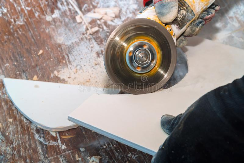 Worker cutting tile using grinder cut into layers of ceramic floor tiles. Worker cutting a tile using grinder cut into layers of ceramic floor tiles flooring stock photography