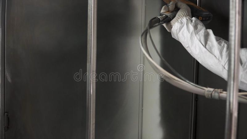 Worker at factory painting metal details with a gun of powder coating. Clip. Construction worker spray paints while. Wearing respiratory safety equipment to royalty free stock photo