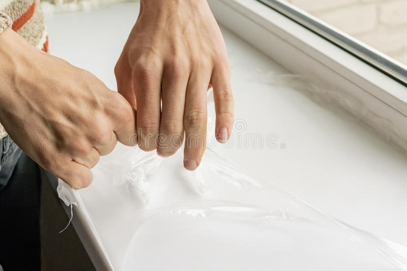 A worker removes plastic film from the window sill stock photography