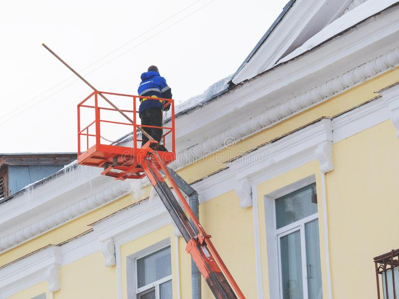 Worker removes snow and ice from the roof of the building stock photo