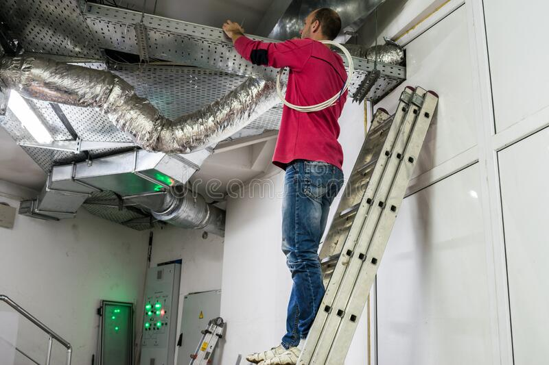 A worker standing on the stairs repairs the ventilation in the technical room of the residential complex. The installer works royalty free stock photos