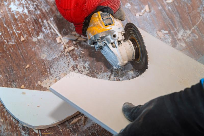Worker using an grinder cutting a floor tile. Worker hand cutting ceramic floor paving tile with electric angle grinder flooring construction material tool tiler royalty free stock images
