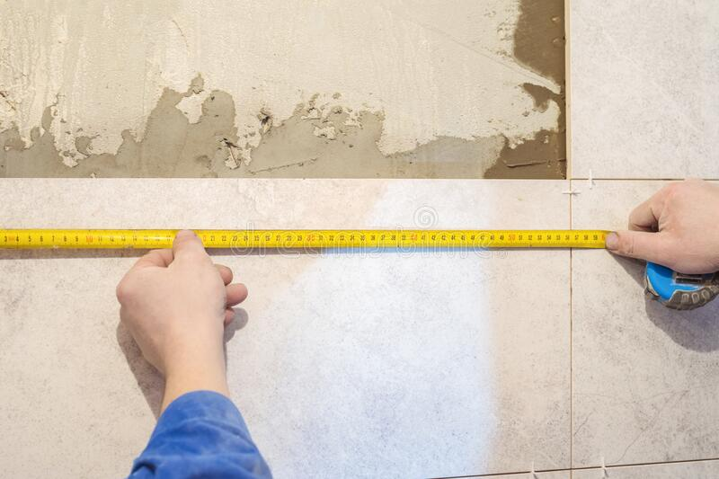 Workers hands and measuring tape. Construction repair work in the room for laying ceramic tiles stock photo