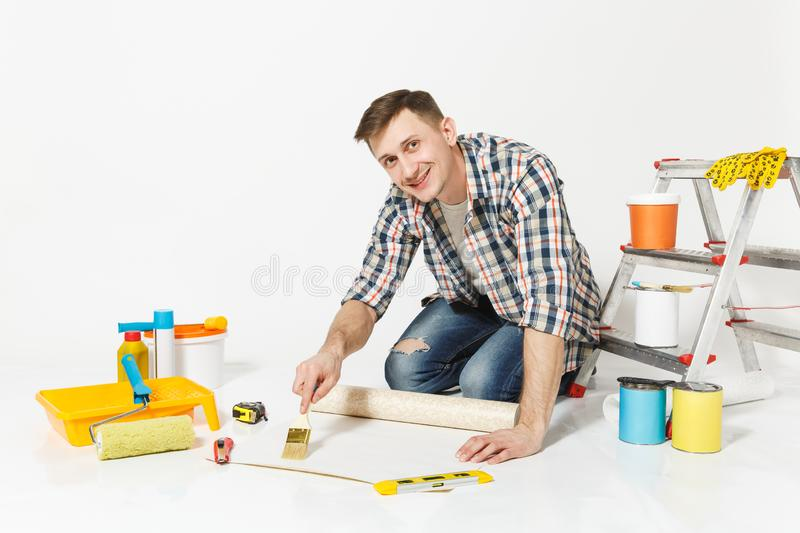 Young man sitting on floor with wallpaper roll, brush for gluing, instruments for renovation apartment room isolated on stock photography