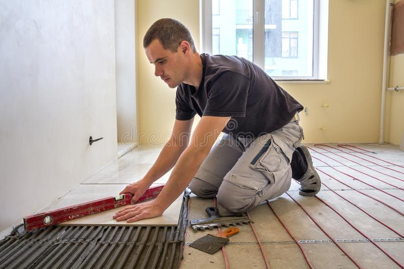 Young worker tiler installing ceramic tiles using lever on cement floor with heating red electrical cable wire system. Home royalty free stock image
