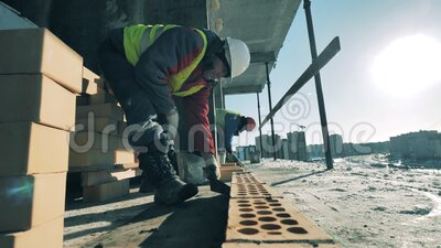 Builders lay bricks on a construction site. stock footage