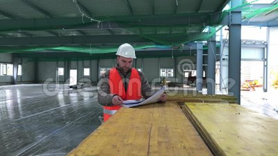 Construction supervisor with plan on site stock footage