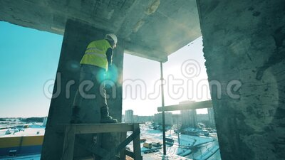 A man works with concrete walls on a construction site. stock video footage