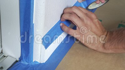 Painter Using Masking Blue Tape to Secure Baseboard, Moulding. Preparation For Room Painting stock video