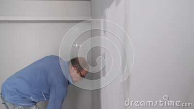 Real senior house painter painting a grey wall with a paint roller. Real dirty worker stock video