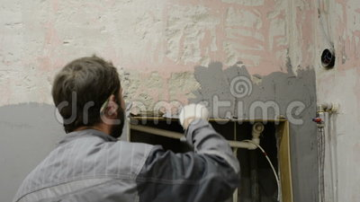 The worker makes plastering of the concrete wall stock footage